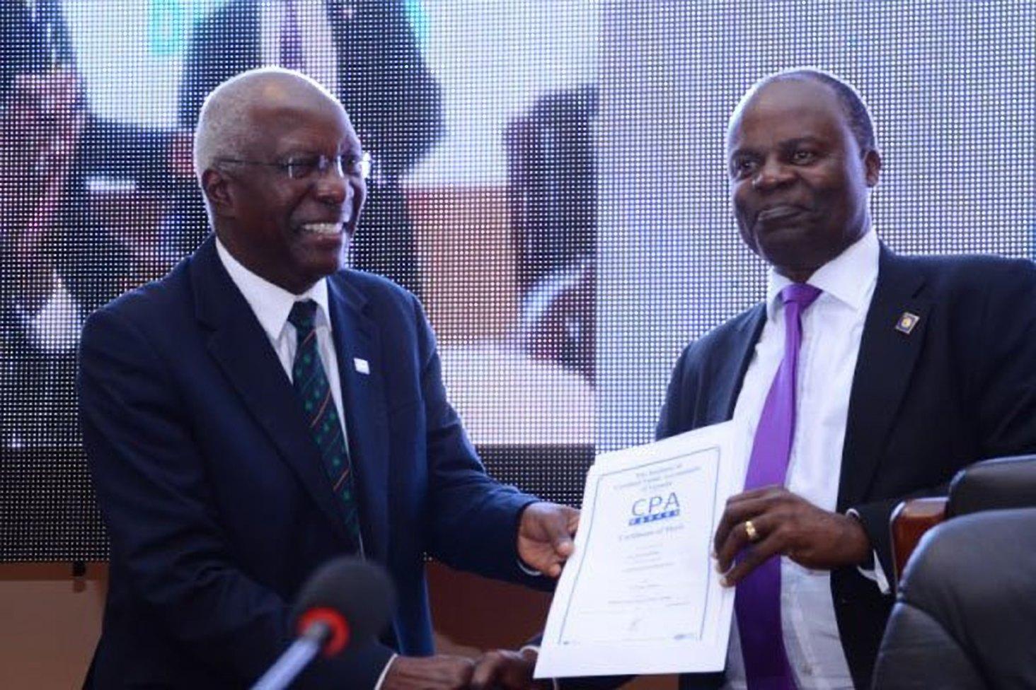 Auditor General John Muwanga (left) hands over certificate to Bank of Uganda deputy governor Louis Kasekende after his keynote address in Entebbe.v1