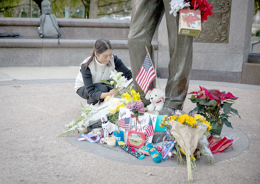 A mourner leaves a card and flowers at a makeshift memorial in tribute to former US President George H. W. Bush at a monument in his honor in Houston, Texas, on December 2, 2018.