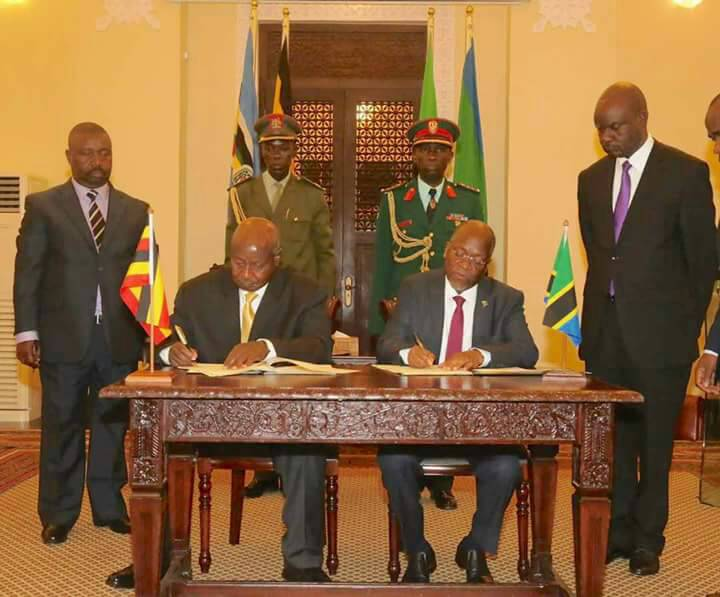 Presidents Museveni and Magufuli sign the deal in Dar on Sunday.