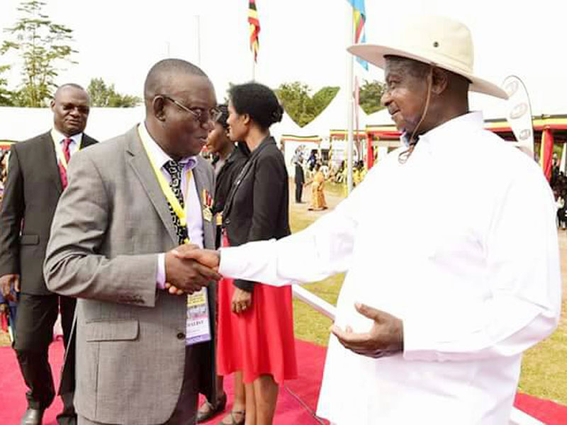 MP Kato Lubwama greets Museveni after his award of a heroes medal on Friday.