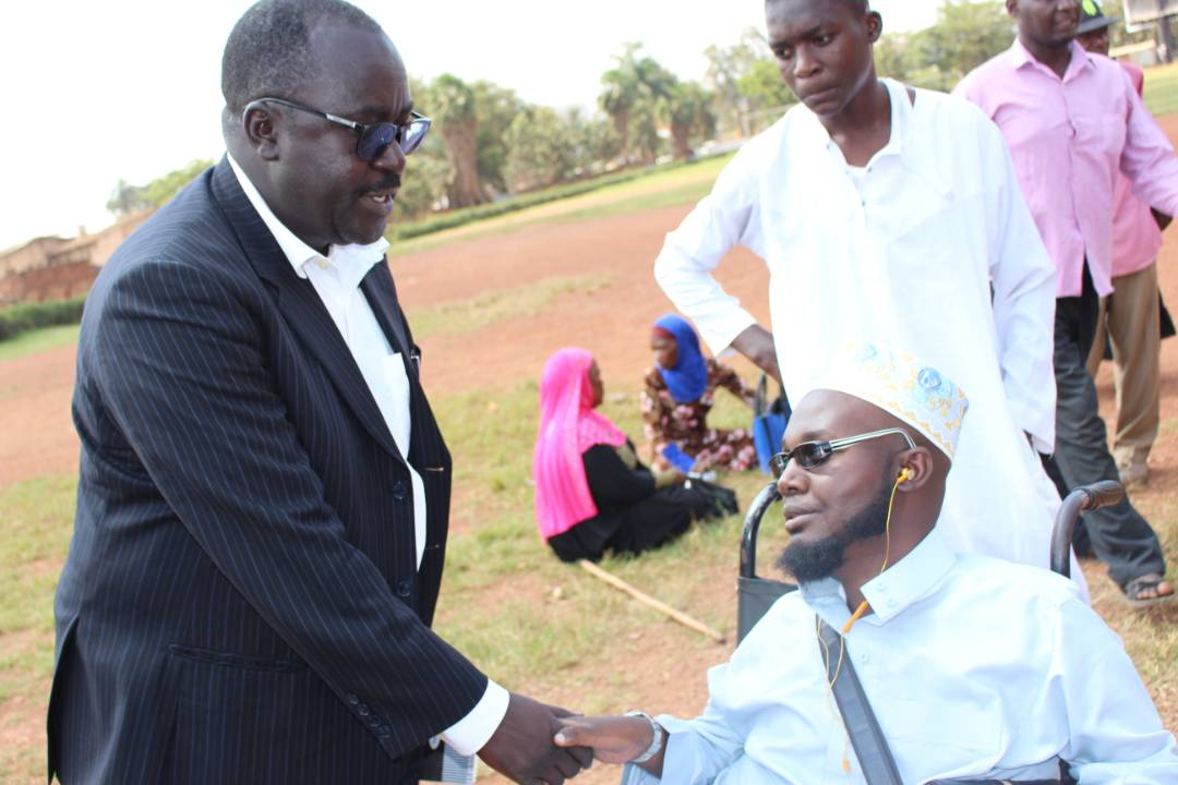 The Public Relations officer of NWSC, Sam Apedel, shares a light moment with one of the disabled Muslims. Courtesy photo