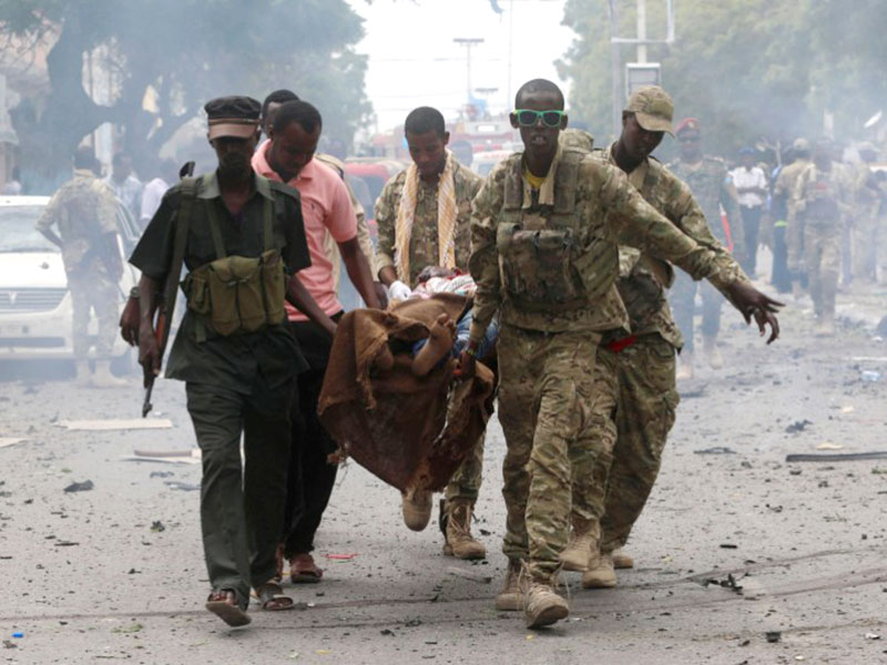 Somali military officers evacuate an injured man from the scene of an explosion in Maka al Mukaram road in Mogadishu, Somalia. Net.