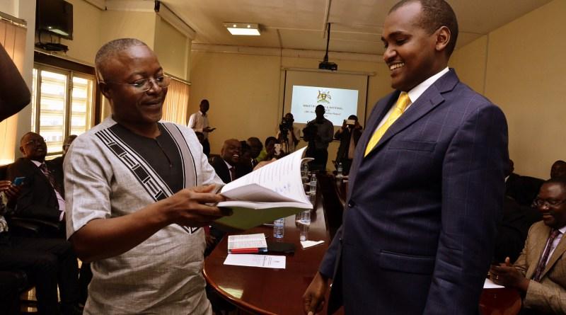 Minister Frank Tumwebaze receives the UBC report from Dr Peter Mwesigye. Courtesy photo.