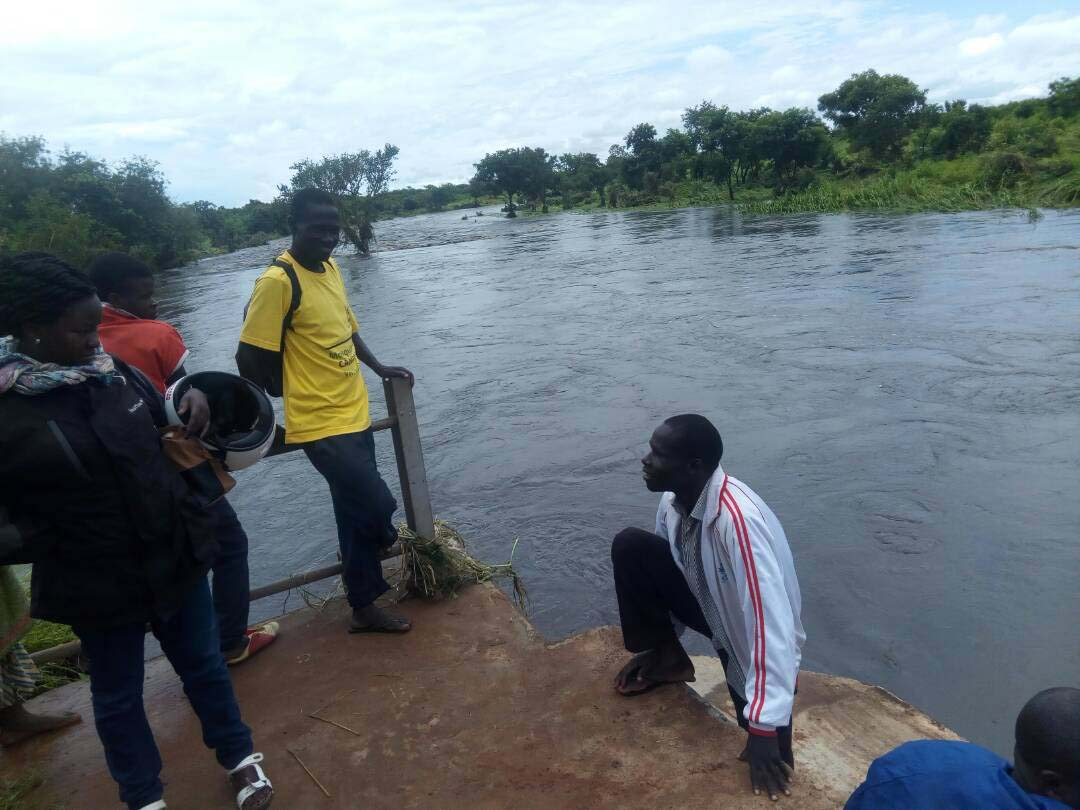 Locals stand on what remains of the bridge on River Unyama in Amuru. Photo by WIlly Chowo.