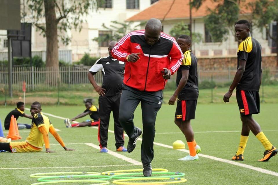 Goal keeping coach Fred Kajoba demonstrates a drill as Mucureezi and Adriko look on. Photo by Shaban Benteke.