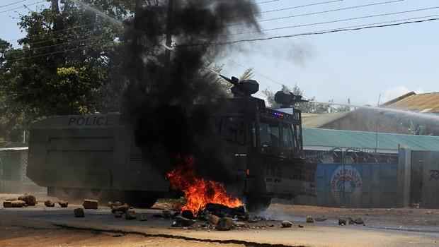 A Kenyan security truck drive past a burning barricade in Kisumu. AP picture.