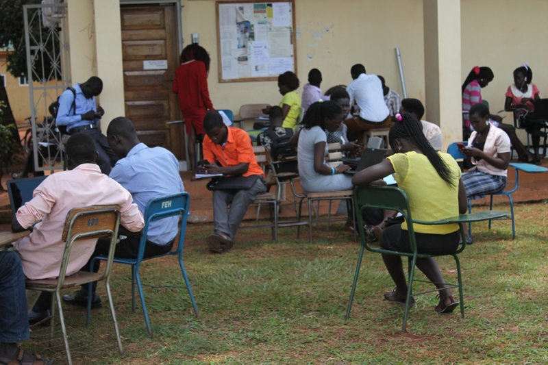 Students read outside closed offices and Library at Gulu University main campus this morning.