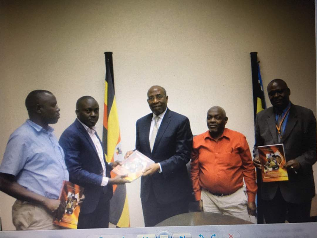 Rugunda recieves a book from Insight Survey Limited employees. Courtesy photo.