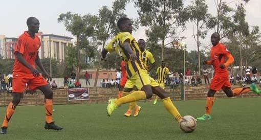 Proline's Saka Mpima clears the ball under pressure from Soana players. Photo by Shaban Lubega.