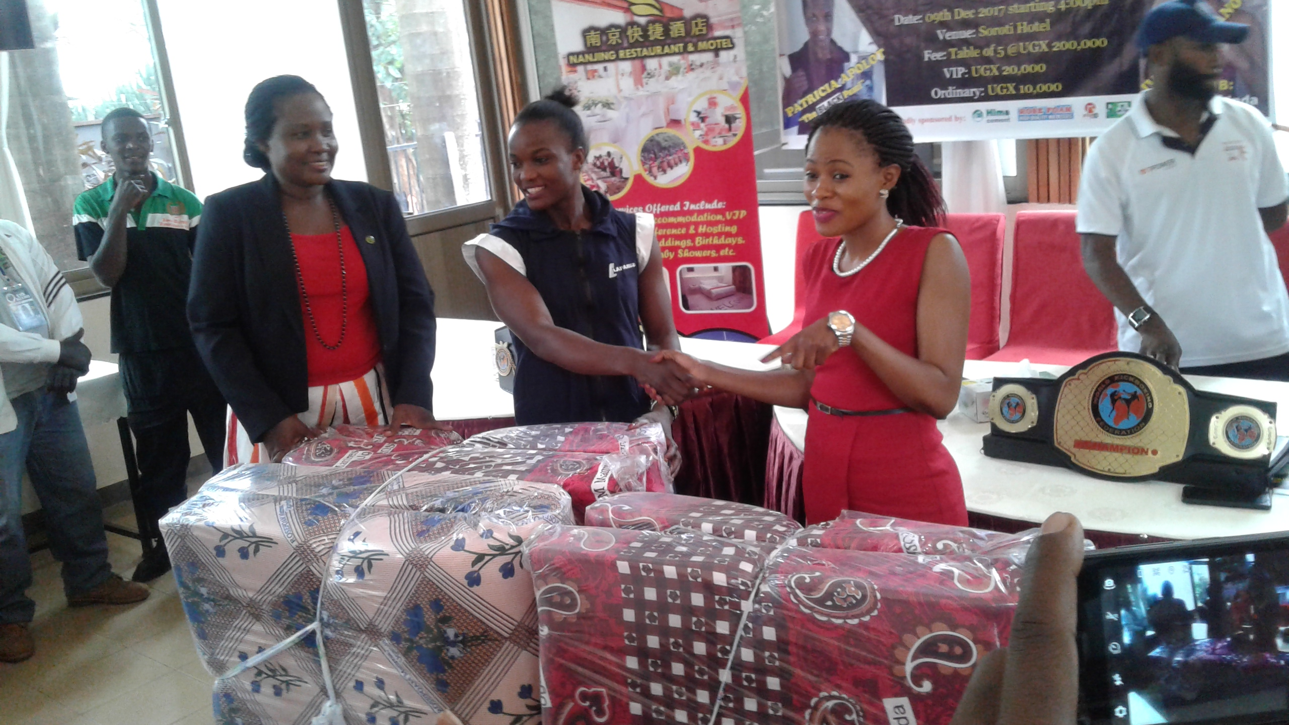 Ross Form PRO Rebecca Kisakye(Right) handing over some of the mattresses to Patricia Opolot.