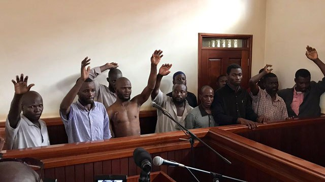 Kaweesi murder suspects stand behind the dock at Nakawa Chief Magistrate's court in Kampala recently. Courtesy Photo