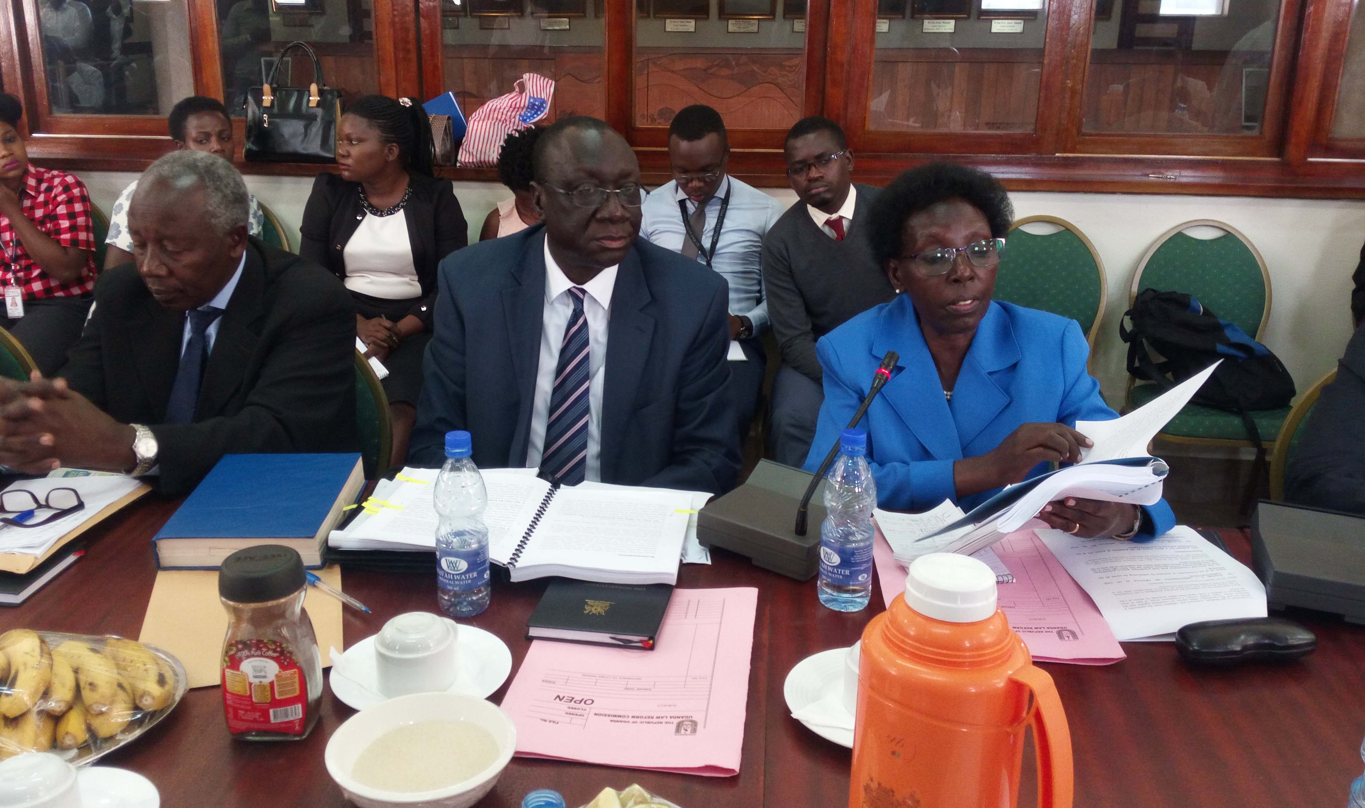 Vastina Rukimirana (right) reads a doucument before the committee, center is Omara Abong secretary to the commission. Please change name in script to RUKIMIRANA