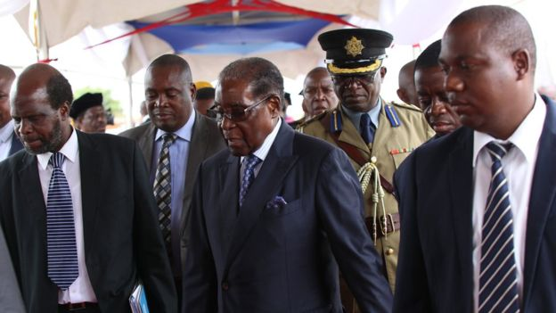Mr Mugabe (Centre) arrives  with a military escort.