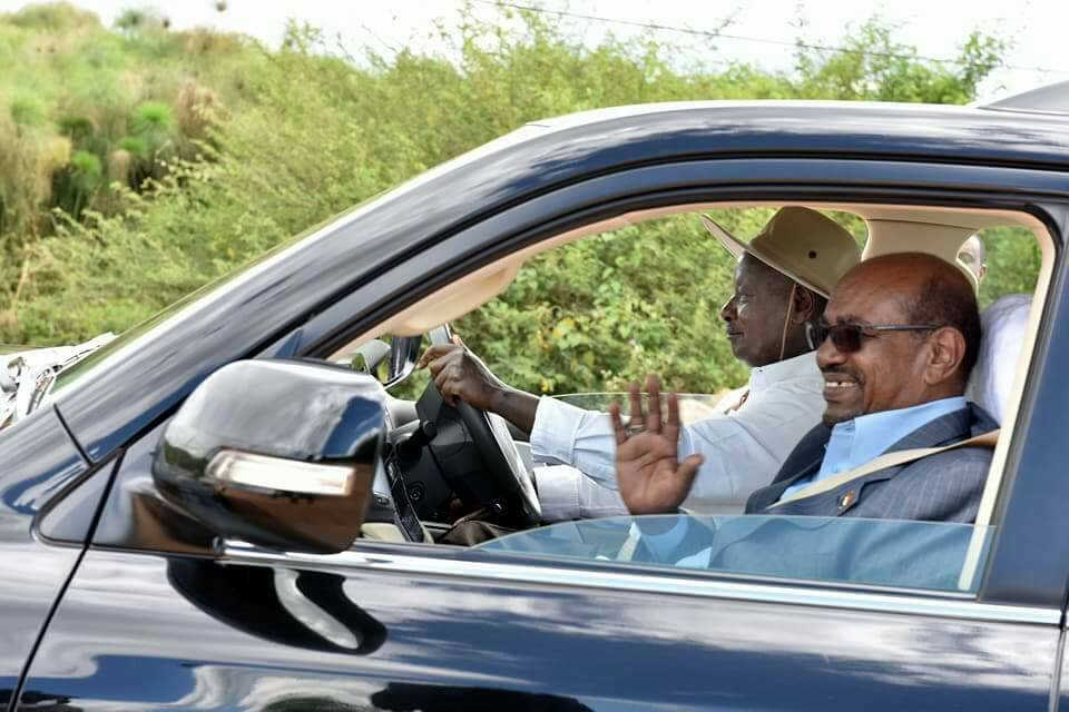 Sudan's President Omar al-Bashir waves as President Museveni drives him around his Kisozi farm. Courtesy photo.