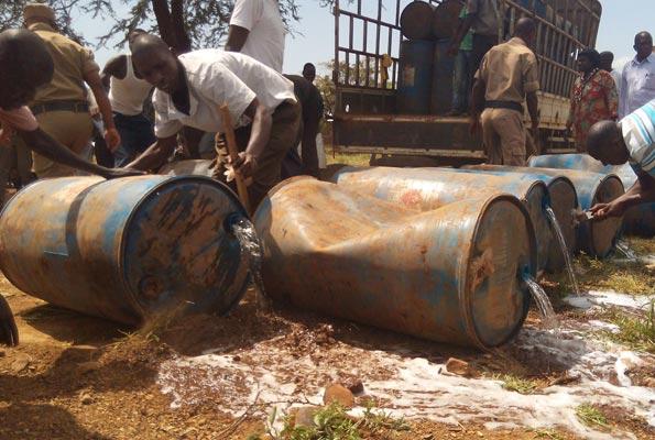 Drums of alcohol being destroyed by policemen in Karamoja. despite this destruction, illicit waragi and sachet waragi finds its way into Karamoja