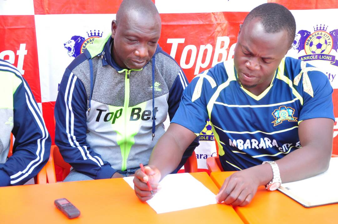 Mbarara City CEO, Saddam Mugalu (right) signing on the one year contract availed to Ibrahim Kirya