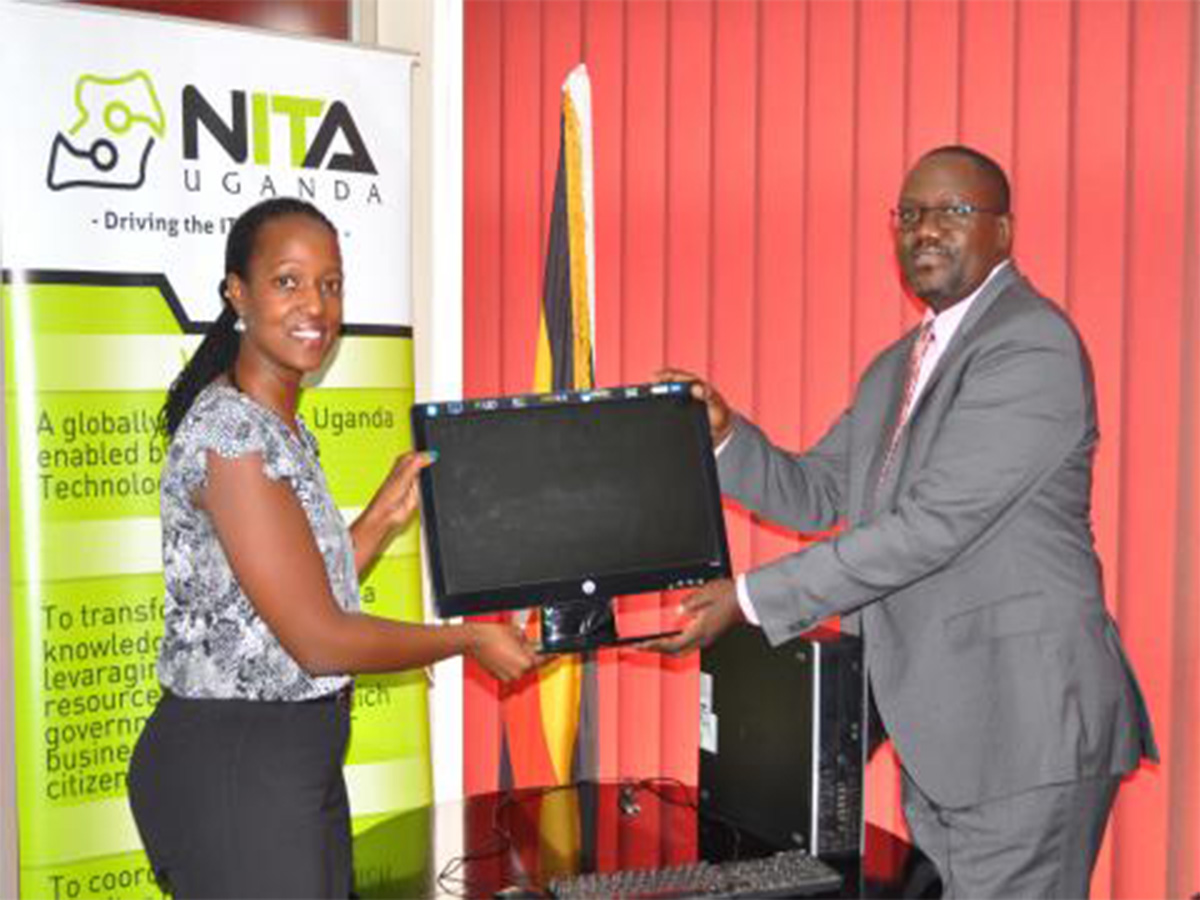 ICT Ministry Permanent Secretary, Vincent Bagiire (R) hands over a computer set to