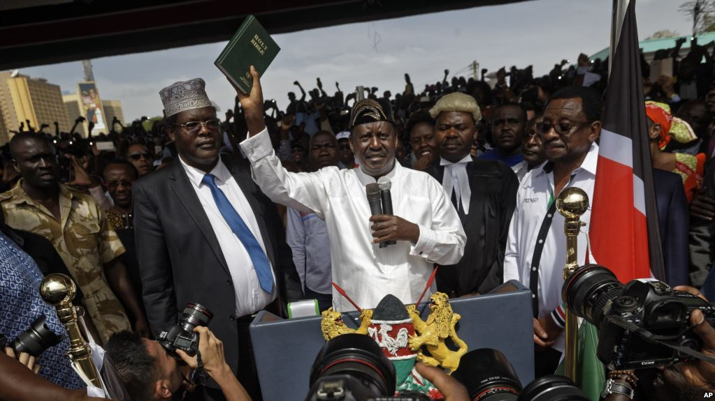 "Opposition leader Raila Odinga holds up a bible during a ""swearing-in"" ceremony: Ageny photo"