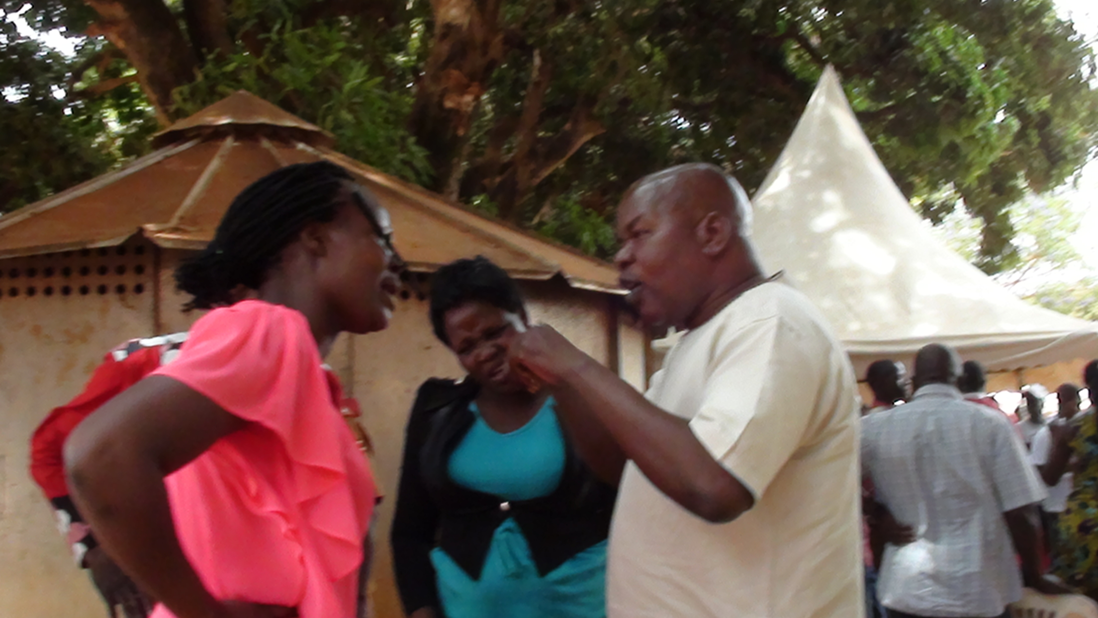 Gulu Mayor, George Labeja calms down Monalisa Aber after she was alledgely kicked by Laroo LCIII Chairman, Moses Abonga.