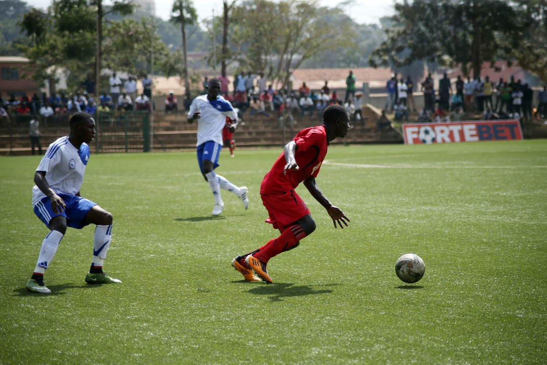 KCCA FC striker Patrick Kaddu dribbles away from a Police defender at Lugogo this afternoon: PHOTO BY SHABAN LUBEGA