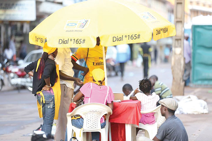 Customers carry out transactions at a mobile money tent. Students sponsored by the government at Makerere have been asked to register their monile numbers to receive allowances through the mobile wallet system.