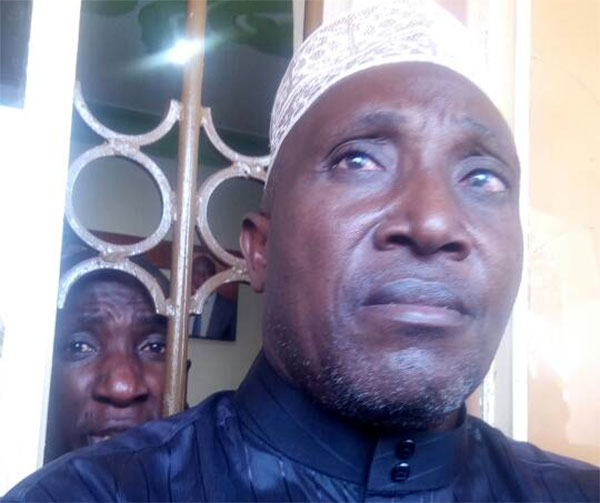 Muhammad Kirumira's father (front) attempts in futility to block the arrest of his son