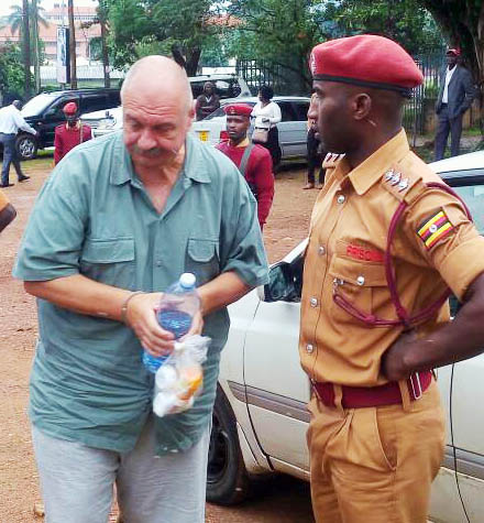 Rogers is guarded by a prison warder at Entebbe Magistrate's court this morning: PHOTO BY RACHEL AGABA
