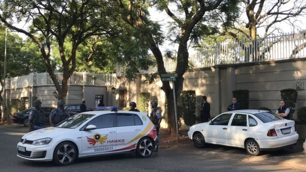 The family's walled Johannesburg compound was subject to an early morning search by elite police.