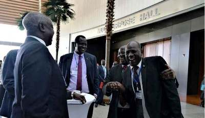 South Sudan information minister Michael Makuei Lueth shakes hands with Lam Akol during the revitalization forum on 19 December 2017: AGENCY PHOTO