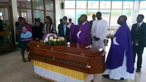 A priest incenses the casket at Mbuya
