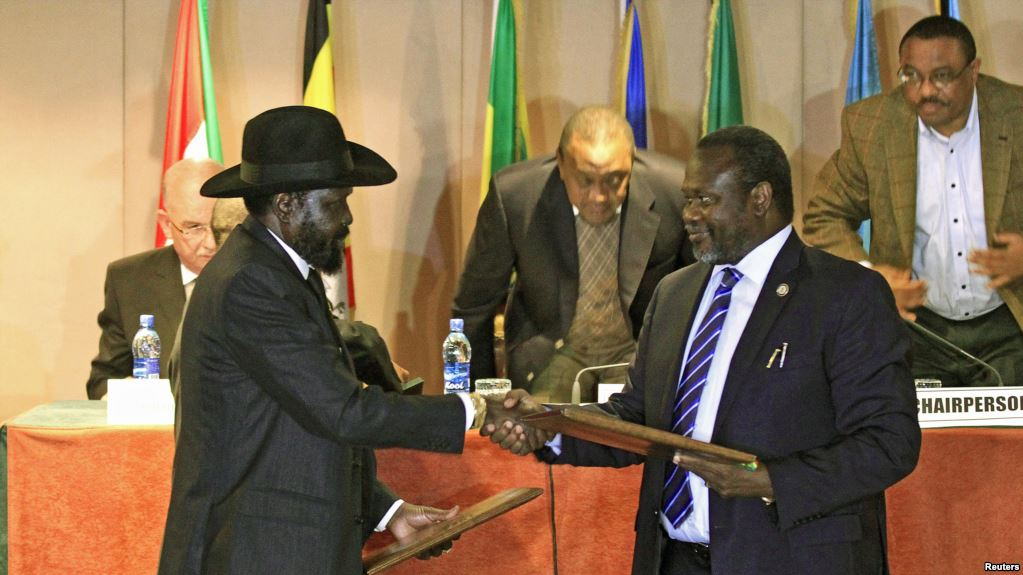 South Sudan's President Salva Kiir (front L) and South Sudan's rebel commander Riek Machar exchange documents after signing a ceasefire agreement during the Inter Governmental Authority on Development (IGAD) Summit on the case of South Sudan in Ethiopia's capital Addis Ababa, Feburary 1, 2015. Kiir and Machar signed another ceasefire agreement on Monday, edging them closer to a final deal to end a 15-month conflict that has ravaged the world's newest country, mediators said. Picture taken February 1, 2015. REUTERS/Tiksa Negeri (ETHIOPIA - Tags: CIVIL UNREST POLITICS CONFLICT) - RTR4NV9Z