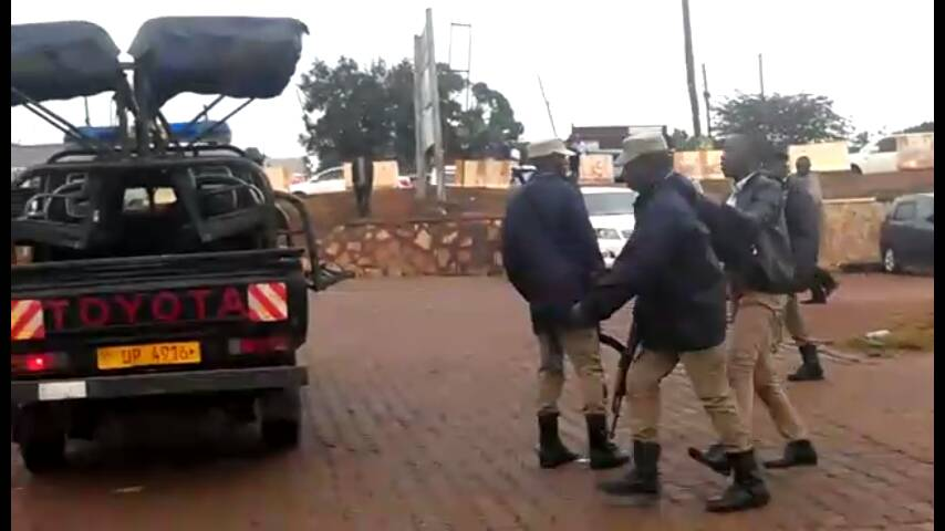 Police officers arrest Kamagu outside Top Radio offices in Kampala on Monday February 19.