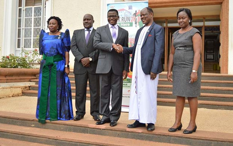 The Katikkiro of Buganda Ow'ekitiibwa Charles Peter Mayiga (C) shakes hands with Vice Chancellor-Prof. Barnabas Nawangwe (2nd R) shortly after accepting the invitation to be the Chief Runner at MakRun2018.