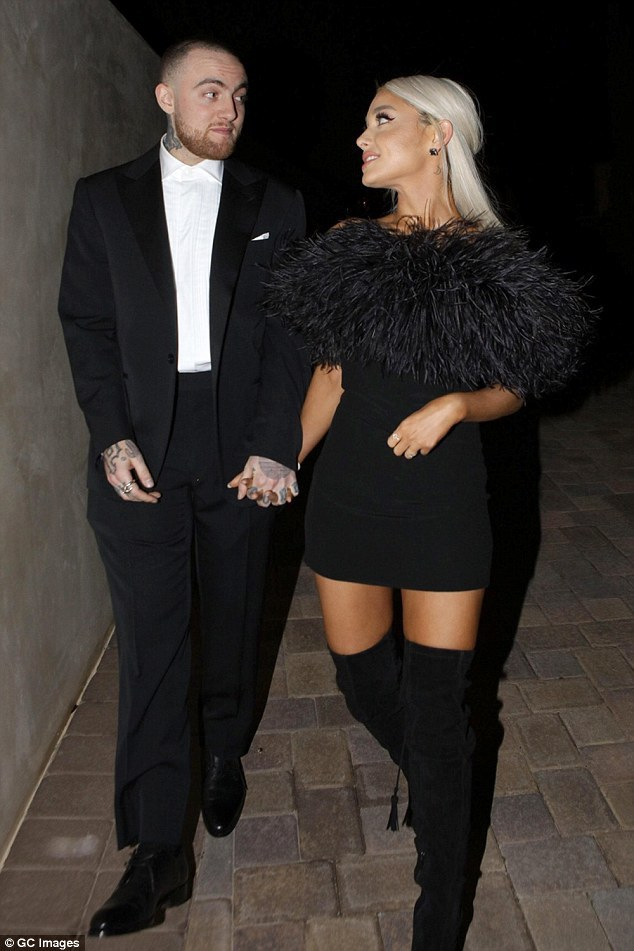 24-year-old Ariana Grande and boyfriend Mac Miller showed up for Madonna's Oscar party in Hollywood Sunday night. She looked stunning in an ostrich-feathered little black dress with over-the-knee black boots. She rocked waist-length platinum blonde hair and held on tight to her rapper boyfriend, 26.