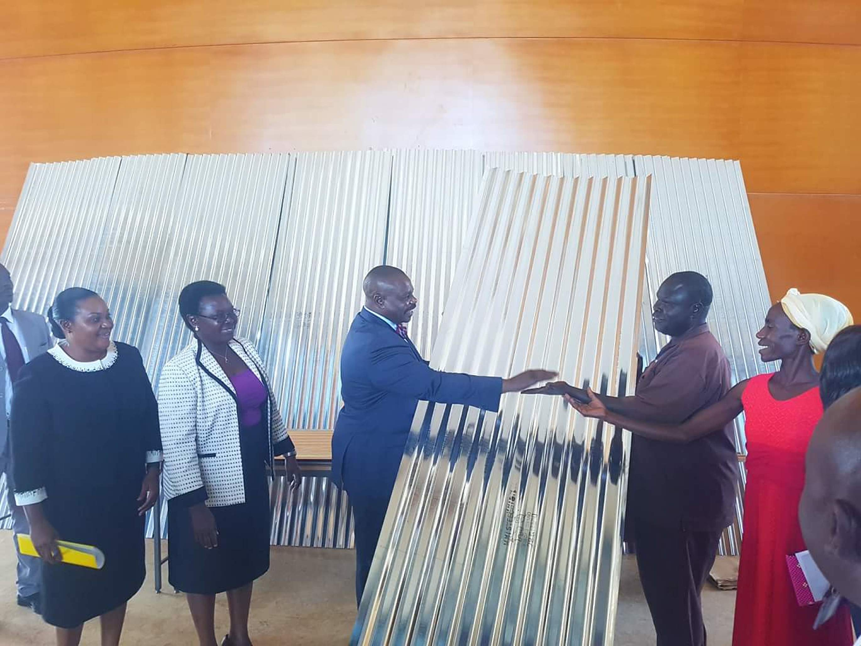 Deputy Speaker, Oulanyah Jacob hands over the iron sheets to the beneficiaries (PML PHOTO)