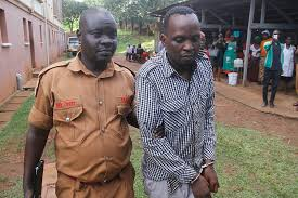 A prison warder leads Kaddu to the prison bus after his past appearance in court.