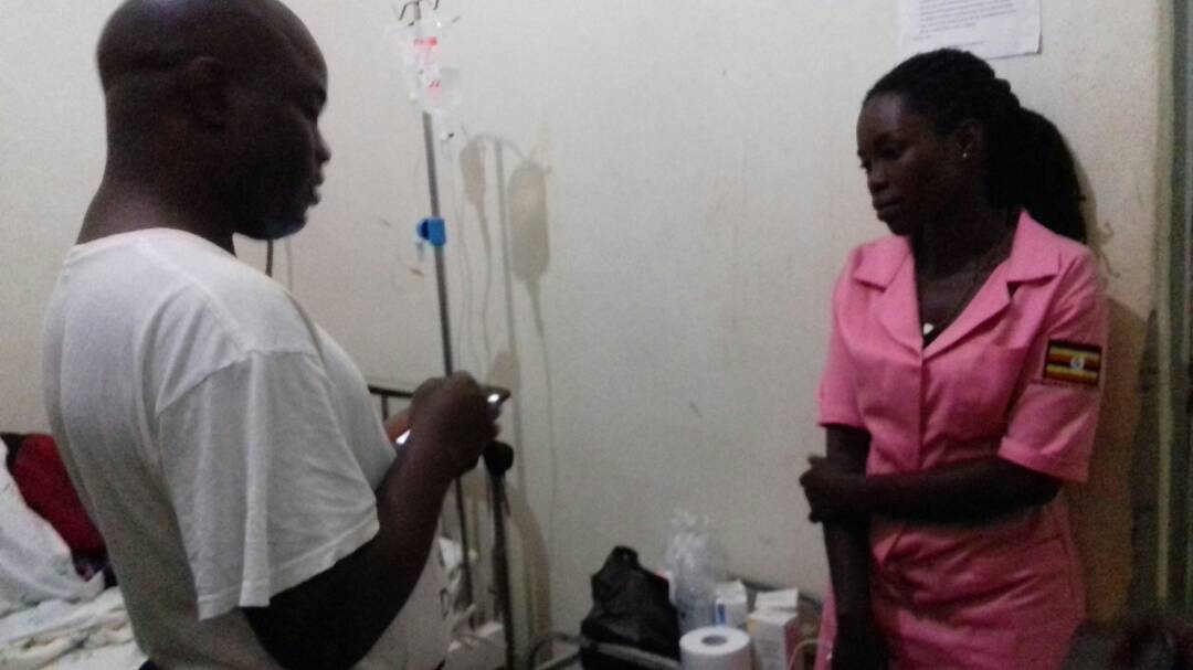 Mr Were Ronald the OC CID Station talking to the nurse on duty Tuesday night at private ward Gulu Regional Referral Hospital. Photo by David Okema.