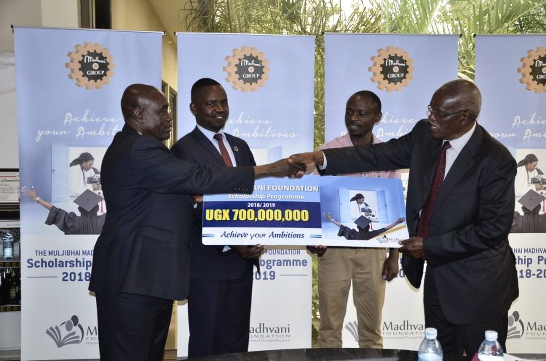 MR. Gerald Ssendawula, the Chairman Madhvani Foundation officially hands over a placard unveiling the 2018/2019 scholarship fund worth ugx 700 million to Hon. Anthony Butele, the chairman of the scholarship committee at Madhvani Foundation (Left). Looking on is Dr. Richard Mugahi, Chairman Alumni Committee (2nd left) and Mr. Innocent Agonza (2nd Right), a 2009 beneficiary of the Madhvani Foundation. (Photo by DMAFABI)