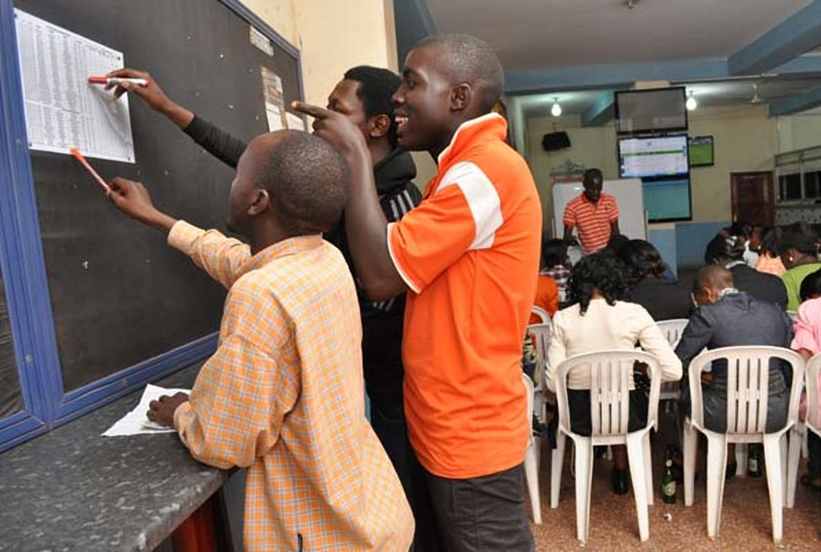 Youths cross check betting odds. Govt to register all sports bettors (COURTESY PHOTO)