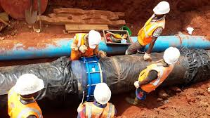 NWSC engineers install a water pipe in Kampala.