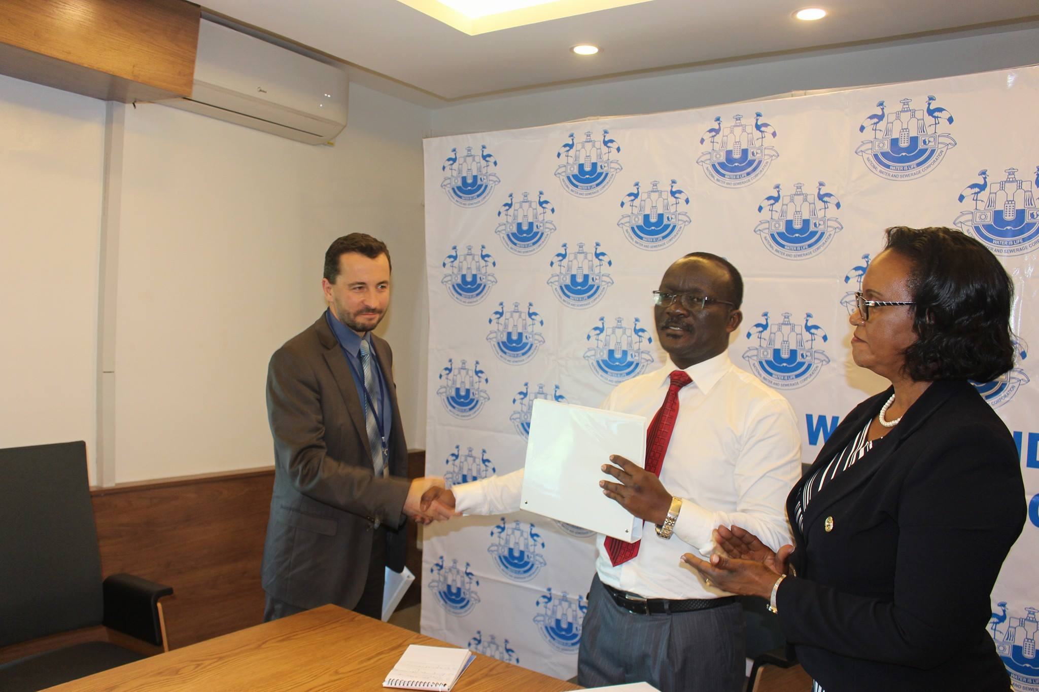 NWSC MD Eng. Dr. Silver Mugisha unveils the contract awarded to SOGEA SATOM, a French company. as their official looks on (Photo: NWSC)