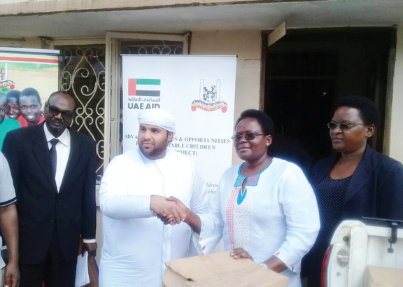 Abdul RaheemObaid Al Falahiincharge De Affairs UAE Embassy handling over donation for fasting children to UWESO CEO Aguti Jennifer at UWESO in Kampala