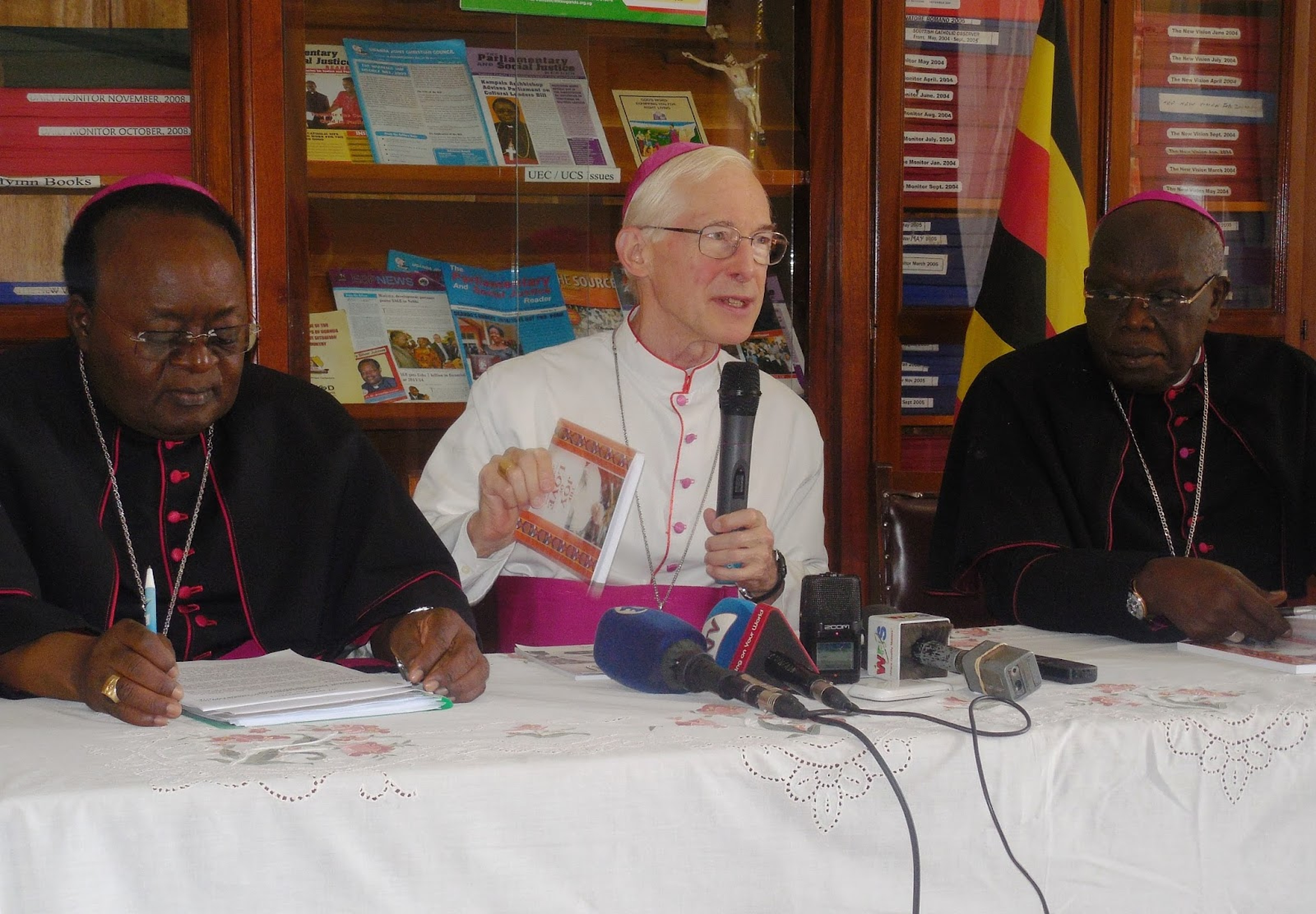 H.E. Most Rev. Michael August Blume, the Former Apostolic Nunci  to Uganda (center) shows to the press a  copy of a booklet  of the Amoris Laetitia. He is flanked by the Chairman  of the Uganda Episcopal Conference and Archbishop of Gulu,  Most Rev. John Baptist Odama (right) and the Archbishop of  Kampala, Most Rev. Cyprian Kizito Lwanga (left)