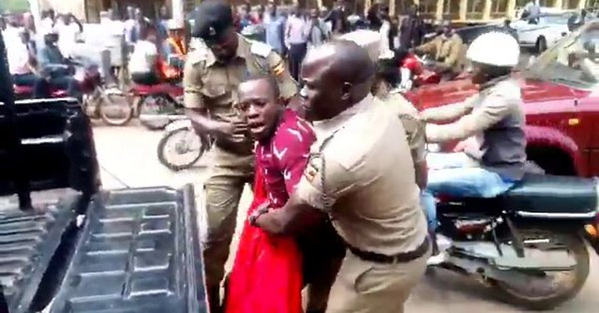 Police officers arrest one of the Makerere students that marched to Parliament in protest of the new social media tax Monday morning