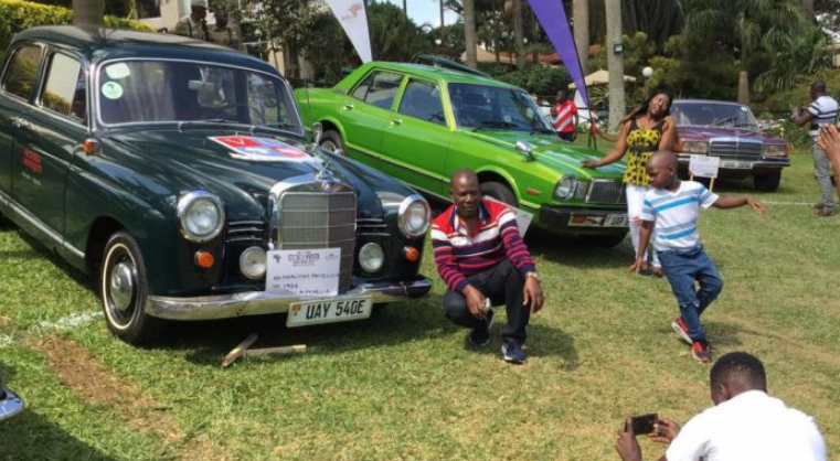 Revellers take turns to share photographs next to the vintage cars at the launch Saturday July 28 (PML Daily PHOTO)