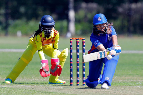 Thailand Batsman Naruemol Chaiwai plays a shot as wicket-keeper captain Kevin Awino watches on (Courtesy Photo)