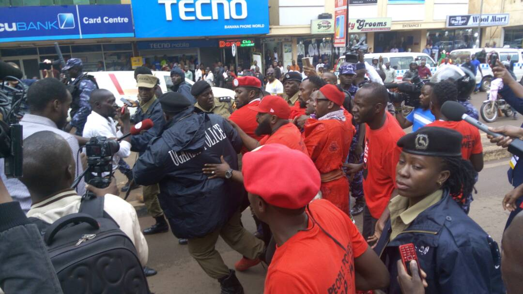 Police officers try to whisk MP Robert Kyagulanyi way from fellow protesters against the new taxes on Wednesday July 11. (PHOTO/File)