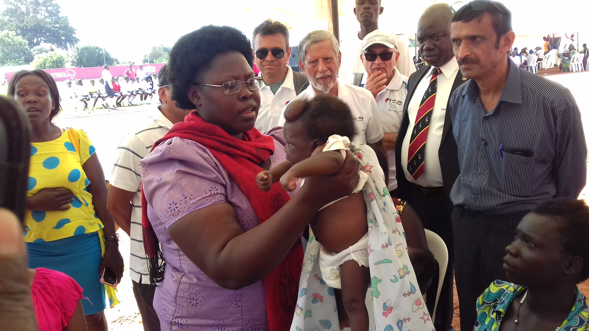 Dr Joyce Kaducu State Minister for Primary Health Care examining a child with swollen head during health camp in Gulu.