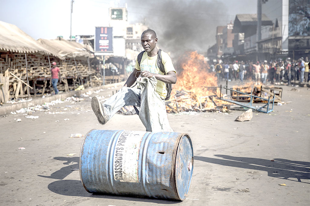 A supporter push a barrel in front of a fire in Harare on Wedensday, as protests erupted over alleged fraud in the country's election.