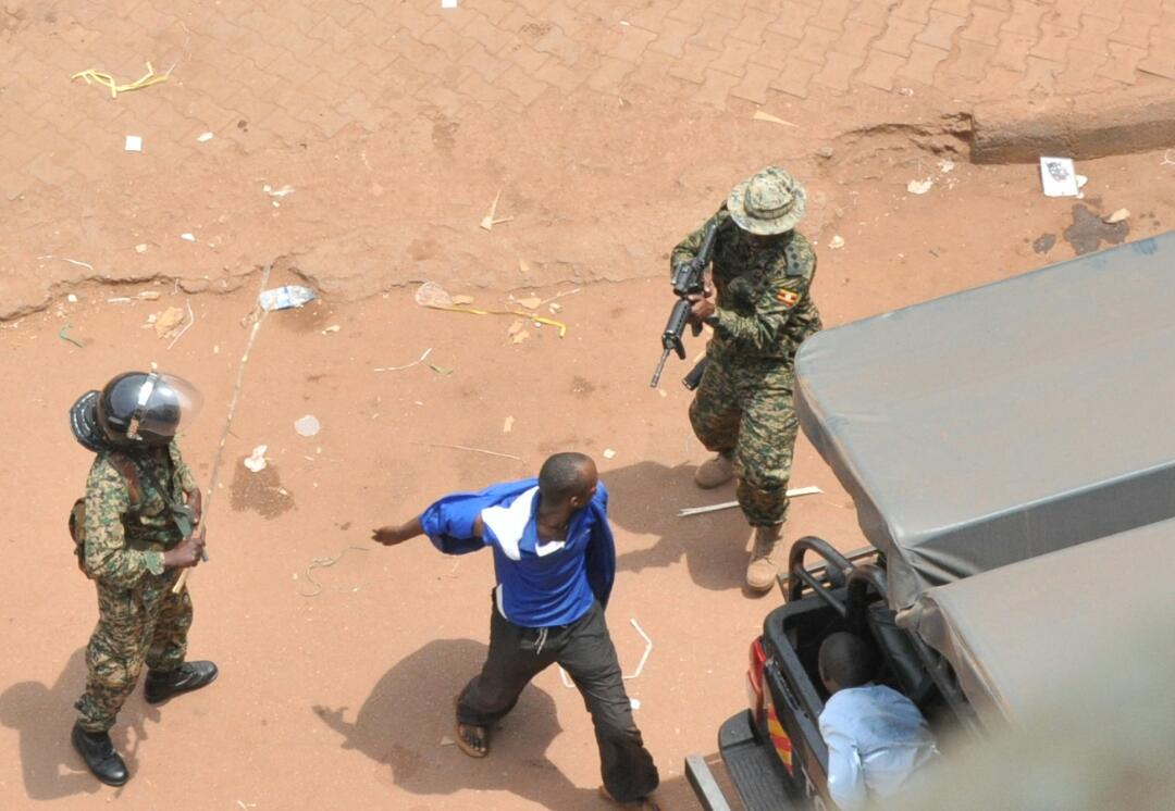 A military officer (Capt by rank) points a gun at one of the protestors at Kiseka Market, Kampala (FILE PHOTO)